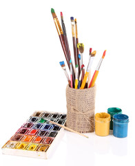 Composition with brushes in vase and paints isolated on white