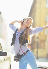 Cheerful young woman listening music in headphones in the city