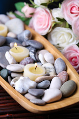 Wooden bowl with spa stones and candles