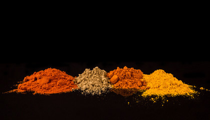 Mix powdered spices on black background