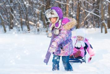 Two cute girls sledding