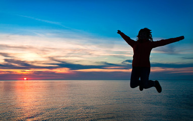 girl jumping on a background of a sunset over the sea