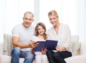 smiling parents and little girl with at home