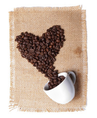 white cup with coffee beans on burlap background. heart symbol.