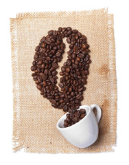 white cup with coffee beans on burlap background