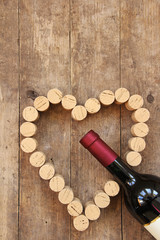 Wine bottle and wine cork on old wooden board
