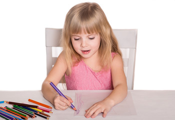 Little girl drawing with crayons.