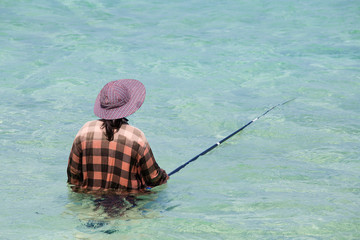 Women with a fishing pole in sea. Thailand.