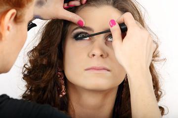 Make-up artist applying makeup at beautiful girl.