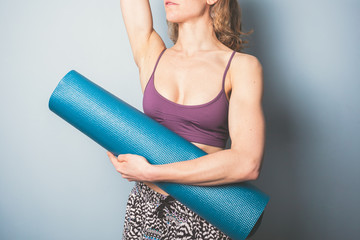 Athletic young woman holding a yoga mat