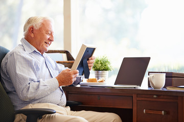 Senior Man Sitting At Desk Looking At Photo Frame