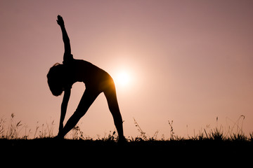 Triangle pose yoga with young woman silhouetted.