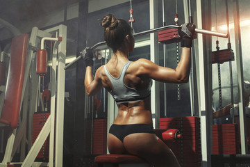 Wall Mural - Woman engaged in the simulator in the gym