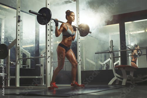 Wall mural Woman lifting weight in gym