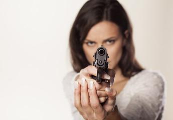 angry girl aiming a gun at you