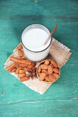 Almond milk in glass with almonds in bowl,