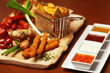 Fried cheese sticks with small meat sausages served with sauces