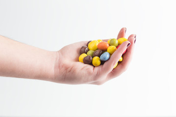 hand with colorful candy Easter eggs
