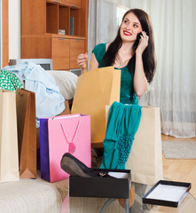 Smiling woman with purchases  speaking by mobile
