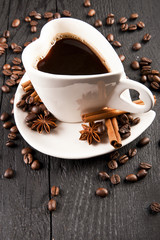 coffee cup in heart shape and coffee beans on dark background