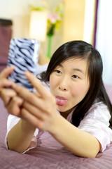 Asian girl having fun making funny faces for selfie