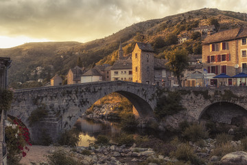 Summer sunset view of a old bridge in a typical French Village