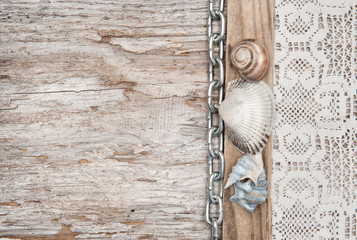 Lace fabric with chain and seashells on the old wood