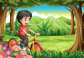 A boy biking at the woods