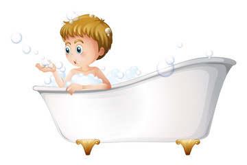 A boy playing at the bathtub while taking a bath