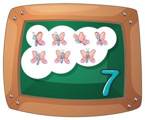 A blackboard with seven butterflies