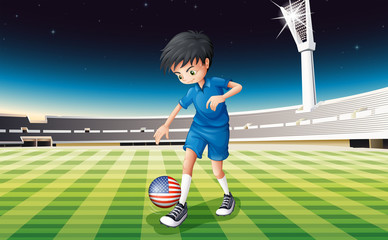 A boy at the field using the ball with the flag of the United St