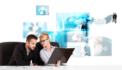Business persons at desk with modern tech images at background