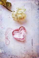 Pink glass heart with dried rose, aged stylized photo
