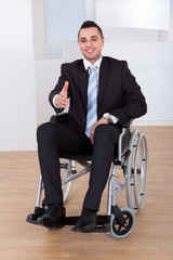 Businessman In Wheelchair Offering Handshake