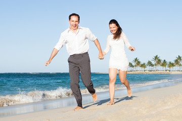 Happy Couple Holding Hands While Running On Beach