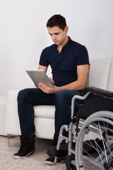 Handicapped Man Using Digital Tablet On Sofa