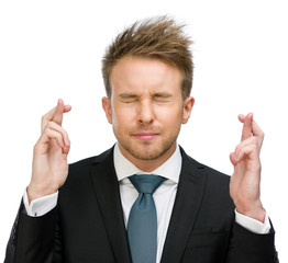 Half-length portrait of businessman with fingers crossed