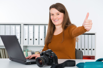 young female reporter in editorial office with thumb up