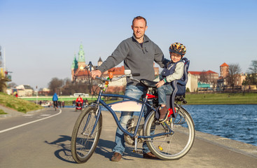 Father with little son walk togeter on bike in city