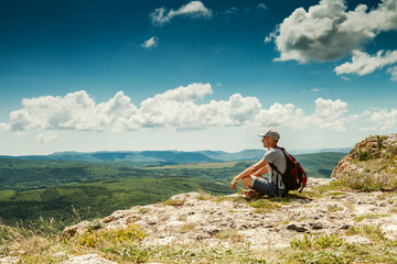 Man hiker with backpack relaxing on top of a mountain