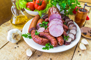 plate various kinds sausages surrounded greens