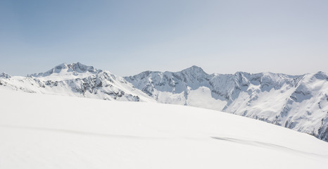 Snow covered slope with mountain ridge in the back