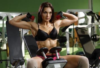 Woman bodybuilder training with dumbbell.