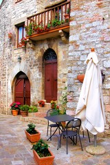 Fotomurales - Table and chairs outside a old trattoria in Tuscany, Italy