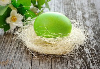 Easter green egg is in a nest on a old wooden background