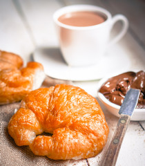 Fresh baked croissants with chocolate cream and hot cocoa on woo