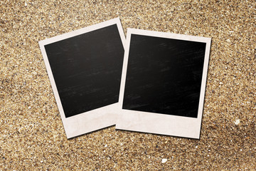blank photo frames laying on sand