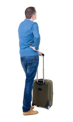Back view of man with  green suitcase looking up.