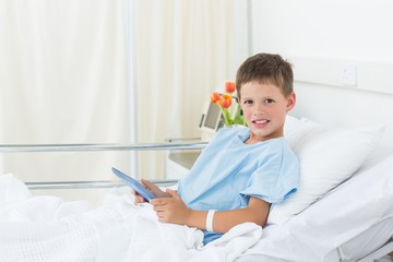 Boy using digital tablet in hospital bed
