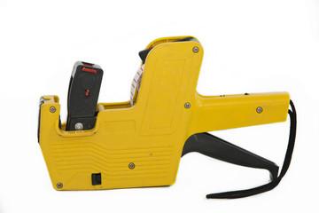 Yellow plastic price label gun on white
